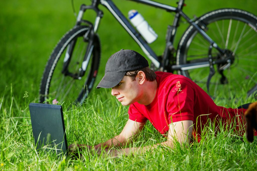 white man browsing online using computer on grasslands with bicycle on the side
