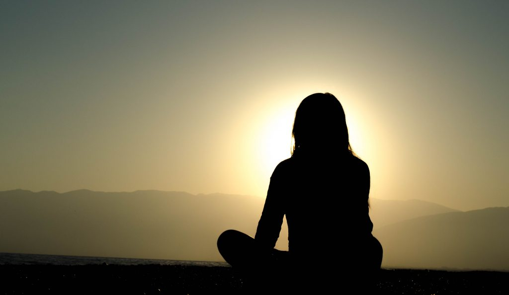 woman thinking in front of a sunrise