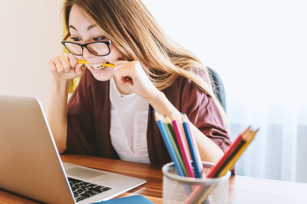woman biting a pencil in front of a laptop