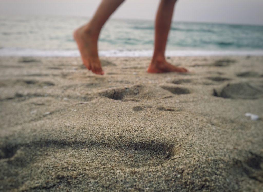 feet stepping in sand