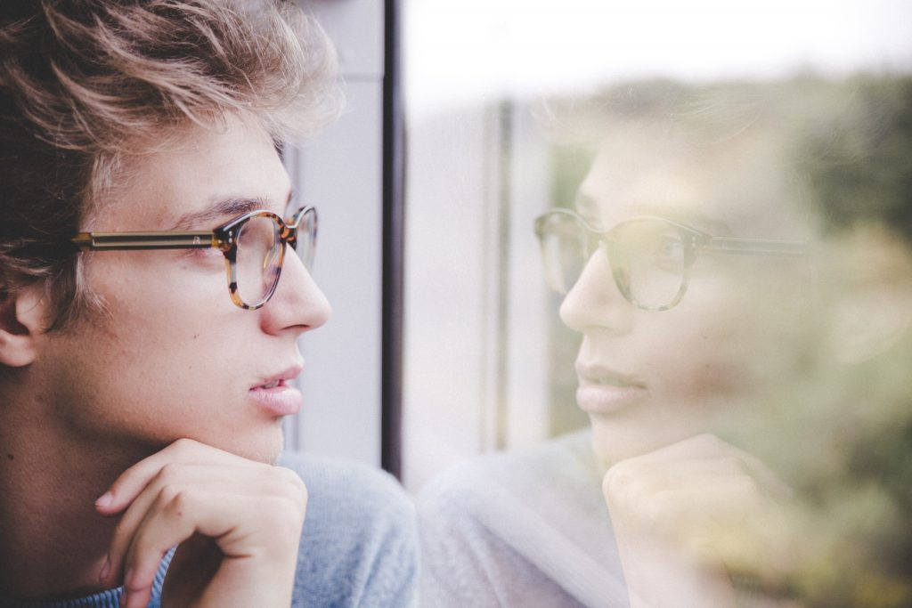 man thinking in front of window