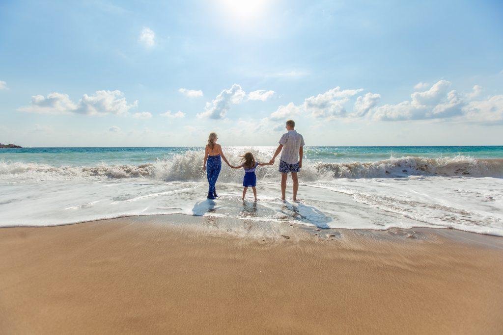 family walking in the seashore